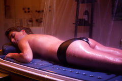 Lying relaxed woman during spa treatment. Color Therapy. Stock Photos