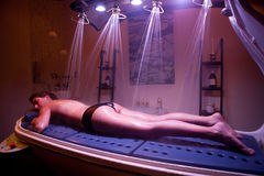 Lying relaxed woman during spa treatment. Color Therapy. Royalty Free Stock Photo
