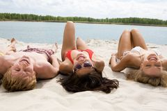 Lying on sand. Photo of pretty girls and a guy lying on sandy beach and looking at camera with smiles Royalty Free Stock Photo