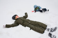 Lying in snow. A mother and her child lying in snow, having fun Royalty Free Stock Photo