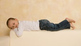 Lying on a sofa. Portrait of a cute boy lying on a sofa Stock Images