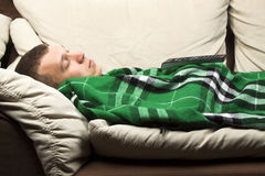 Lying on the sofa. A young man sleeping on the couch with remote control royalty free stock images