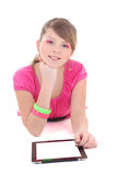 Lying teenage girl in pink with tablet pc Stock Photos