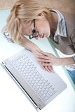 Lying tired next to laptop Stock Photo