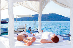 Lying on white bed at the sea Stock Photography