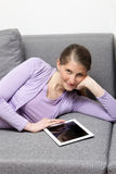 Lying woman on brown couch Stock Photo