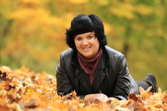 Lying woman in fallen leaves Stock Photos