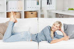 Lying woman listening to music Stock Images