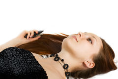 Lying woman with long hairs and comb Stock Image