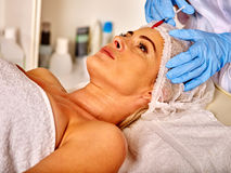 Lying woman middle-aged in spa salon with beautician. Woman gets botox injections. Stock Photo