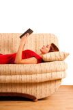 Lying woman in red shirt reading book. Detail. Beautiful woman in a red shirt is lying on the back and reading a book stock image