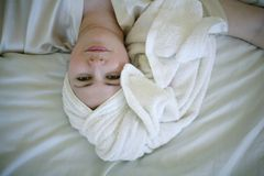 Lying woman in robe and towel. Woman lying down with towel wrapped around head Stock Photography