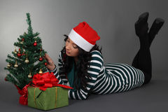 Lying woman in santa hat with gift and tree Stock Images