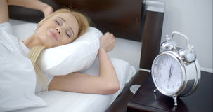 Lying Woman Turning Off an Alarm Clock. Close up Lying Pretty Woman Turning Off a Noisy Alarm Clock Next to her Bed stock footage