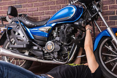 Lying Young Guy Fixing his Sports Motorbike Stock Images
