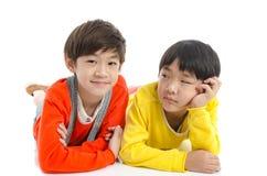 Lyinig asiático lindo de los niños en el fondo blanco fotos de archivo libres de regalías
