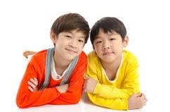 Lyinig asiático lindo de los niños en el fondo blanco foto de archivo libre de regalías