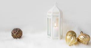 Lykta för vit jul med den vita stearinljuset och guld- bollar på wh Royaltyfri Fotografi