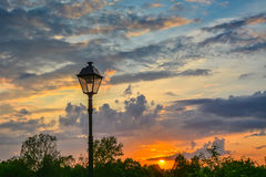 Lykta i retro stil på en bakgrund av en färgrik solnedgång Royaltyfri Fotografi