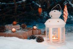 Lykta med en brinnande stearinljus och slågna in gåvor i snön under julgranen på julafton arkivbild