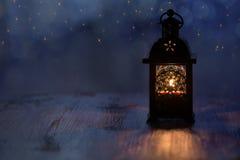 Lykta med stearinljus och guld- stjärnor på en blå bakgrund Härlig bakgrund för julferierna Arkivfoton