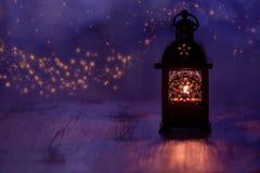 Lykta med stearinljuset på en härlig blå bakgrund med stjärnor vita röda stjärnor för abstrakt för bakgrundsjul mörk för garnerin Fotografering för Bildbyråer