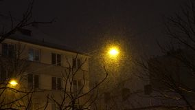 Lyktan skiner på natten under ett snöfall arkivfilmer