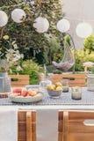 Lyktor ovanför tabellen med mat och drinken i trädgården med växter och trästolar Verkligt foto royaltyfria bilder