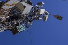 Lyktstolpe med ett tilltrasslat telekommunikationsystem Tråd exploaterar och föreningspunktaskar Hus arkivbild