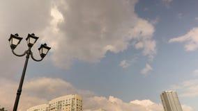 Lyktstolpe och stads- arkitektur Ryssland Saratov Moln som kör till och med blå himmel Time-schackningsperiod inspelning Längd i  stock video