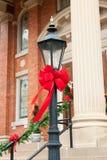 Lyktstolpe som dekoreras med det röda bandet för jul Royaltyfria Bilder
