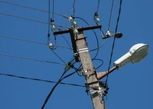 Lyktstolpe, trådar och isolatorer på bakgrunden av en ljus blå himmel royaltyfri bild