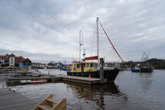 Lymington Harbour. With boat at berth, angry sky Stock Image