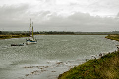 Lymington Nature Reserve. A sailing ship moored on the salt flats at Keyhaven Marsh, part of the Lymington Nature Reserve in Hampshire, England Stock Photography