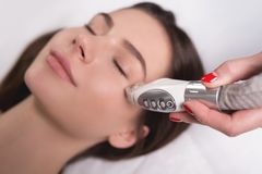 Lymphatic drainage massage LPG apparatus process. Therapist beautician makes a rejuvenating facial massage for the woman royalty free stock photos