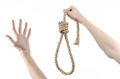 Lynchen- und Selbstmordthema: die Hand des Mannes, die eine Schleife des Seils für das Hängen am Weiß hält, lokalisierte Hintergr Stockfotos