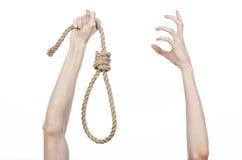Lynchen- und Selbstmordthema: die Hand des Mannes, die eine Schleife des Seils für das Hängen am Weiß hält, lokalisierte Hintergr Lizenzfreies Stockbild
