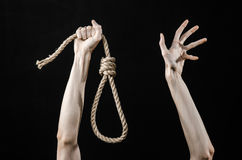 Lynching and suicide theme: man's hand holding a loop of rope for hanging on black isolated background Stock Images