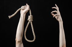 Lynching and suicide theme: man's hand holding a loop of rope for hanging on black isolated background. Studio Royalty Free Stock Photography