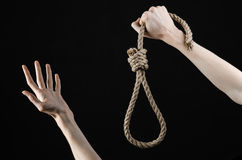 Lynching and suicide theme: man's hand holding a loop of rope for hanging on black isolated background Stock Image