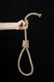 Lynching and suicide theme: man's hand holding a loop of rope for hanging on black isolated background. Studio Royalty Free Stock Images