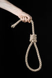 Lynching and suicide theme: man's hand holding a loop of rope for hanging on black isolated background. Studio Stock Photos