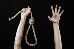 Lynching and suicide theme: man's hand holding a loop of rope for hanging on black isolated background. Studio Royalty Free Stock Photo