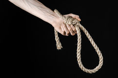 Lynching and suicide theme: man's hand holding a loop of rope for hanging on black isolated background. Studio Stock Image