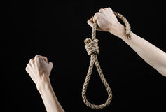 Lynching and suicide theme: man's hand holding a loop of rope for hanging on black isolated background. Studio Royalty Free Stock Image