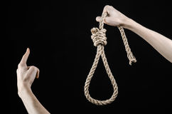 Lynching and suicide theme: man's hand holding a loop of rope for hanging on black isolated background Royalty Free Stock Images