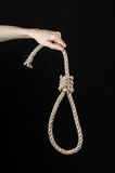 Lynching and suicide theme: man's hand holding a loop of rope for hanging on black isolated background. Studio Royalty Free Stock Photos