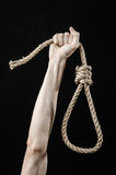 Lynching and suicide theme: man's hand holding a loop of rope for hanging on black isolated background Royalty Free Stock Photography