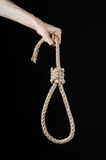 Lynching and suicide theme: man's hand holding a loop of rope for hanging on black isolated background Stock Photos