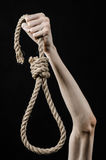 Lynching and suicide theme: man's hand holding a loop of rope for hanging on black isolated background. Studio Stock Images